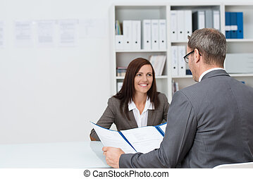 Businessman conducting an employment interview with an attractive young female applicant sitting opposite him at the desk in the office answering his question concerning her CV