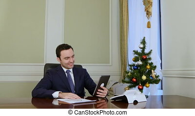 Businessman congratulates business partners with Christmas via internet with tablet
