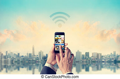 Businessman connecting mobile payments to Wifi network in the city