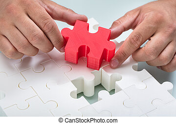 Businessman connecting red piece into white jigsaw puzzles