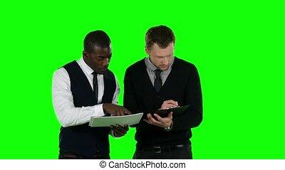 Businessman considering documentation. Green screen
