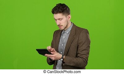 Businessman considers money on a calculator and is happy that he has income. Green screen