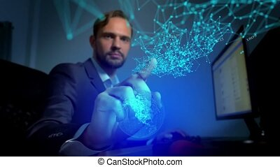 businessman controls the hologram of the globe, looking at the spread of information in the network