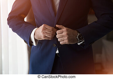 Businessman corrects buttons on his jacket, hands close-up,...