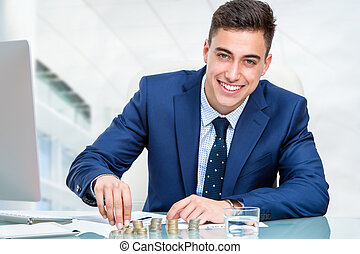 Businessman counting money at desk.