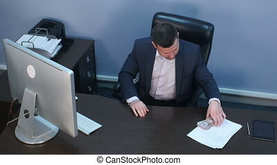 Businessman counting money dollars at the office