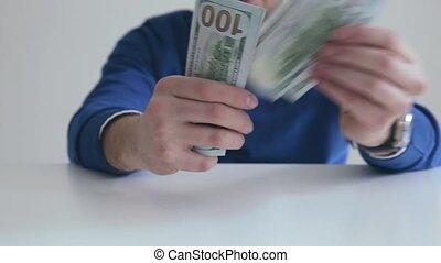 Businessman counts hundred dollar bills