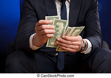 Businessman counts money in hands.