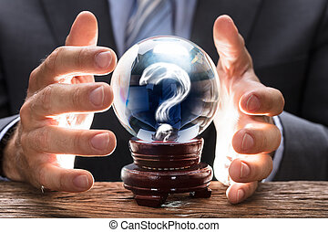 Businessman Covering Crystal Ball With Question Mark