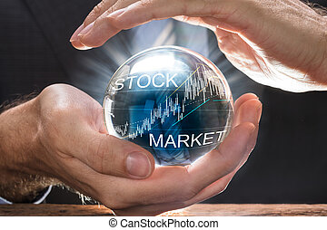 Businessman Covering Crystal Ball With Stock Market Graphs -...
