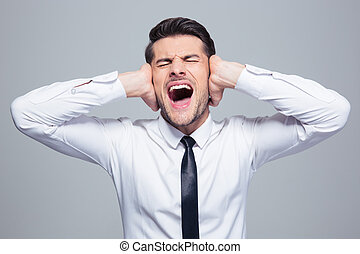 Businessman covering his ears and screaming over gray...