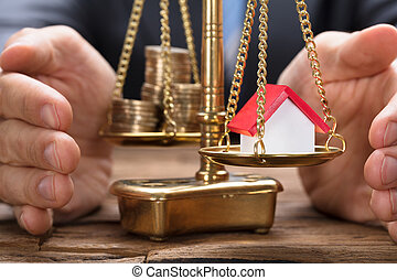 Businessman Covering Model Home And Coins On Weighing Scale