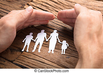 Businessman Covering Paper Family At Wooden Table