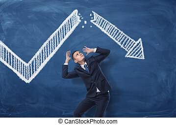 Businessman cowering on blue blackboard background with chalk drawing of white statistic arrow broken in half.