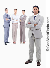 Businessman crossing his arms with serious people in background against white background