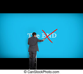Businessman crossing out the word end on a giant blue wall