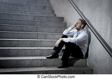 businessman crying lost in depression sitting on street...