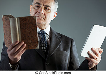 Businessman deciding between a book or e-book