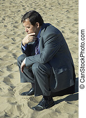 businessman deep in thought on the sand