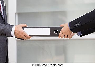 Businessman delivering documents to businessman