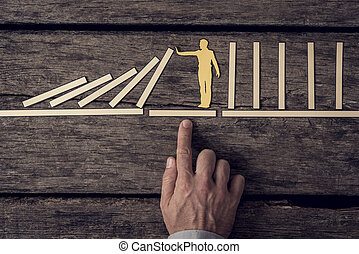 Businessman demonstrating stopping the domino effect