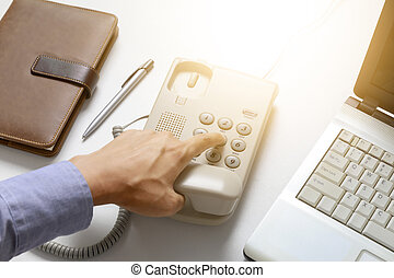 businessman dial digital telephone with office background