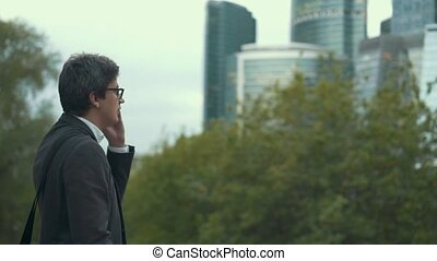 Businessman dialing a phone and talking in a city,...