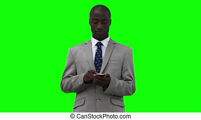 Businessman dialing on his phone before looking upwards