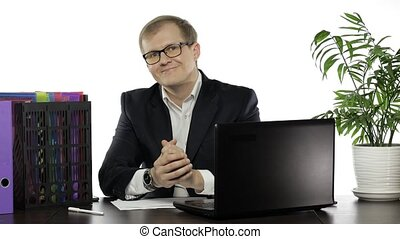 Businessman director in office leaning on table looking at ...
