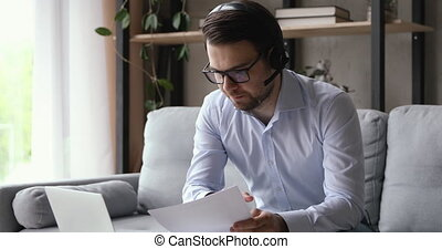 Businessman sit on couch working from home wear headset with microphone talk with client by video call app discuss contract details provide information. Distant negotiations, modern tech usage concept