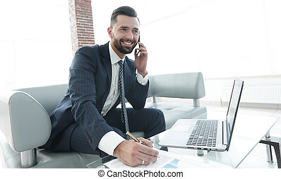 Businessman discussing on a smartphone, business issues with...