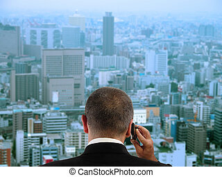 Businessman discussing to the mobile phone in his office while is looking through the window to the city. Focus on the businessman, the city aspect is blurred.