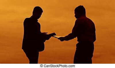 businessman discussion sunset silhouette sunlight standing clipboard concept. two businessman men swearing conflict fight outdoors looking at slow motion video