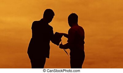 businessman discussion sunset silhouette sunlight standing clipboard concept. two businessman men are in talks looking at slow video outdoors