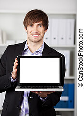 Businessman Displaying Laptop In Office