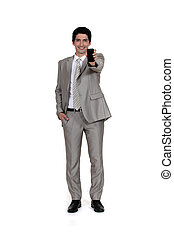 Businessman displaying mobile telephone