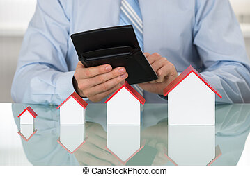 Businessman Doing Calculation On Calculator In Front Of House Model On Desk