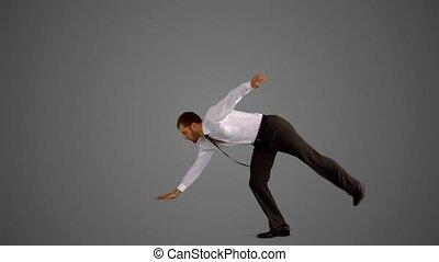Businessman doing one hand handstand
