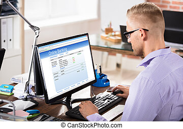 Businessman Doing Online Banking In Office
