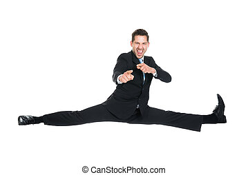 Full length portrait of young businessman doing splits while gesturing over white background