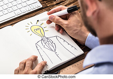 Businessman Drawing A Person With Light Bulb Head