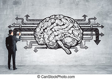 Businessman drawing brain on concrete wall