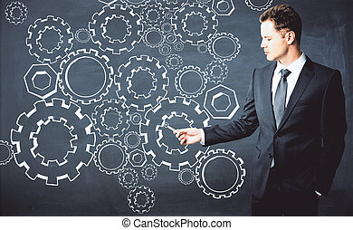 Businessman drawing cogwheels