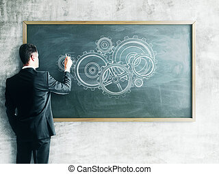 businessman drawing gears on a chalk board