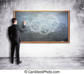 businessman drawing gears and cogs on a chalk board