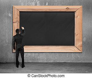 Businessman drawing on blank black chalkboard