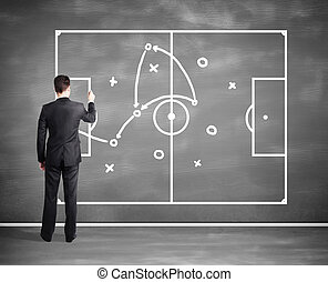 businessman drawing tactic scheme on big black desk board