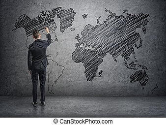 Businessman drawing world map on the concrete wall