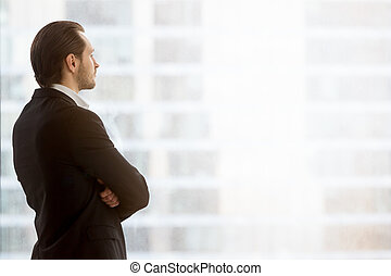 Businessman dreamily looks in window at office