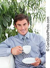 Businessman drinking a cup of coffee on sofa